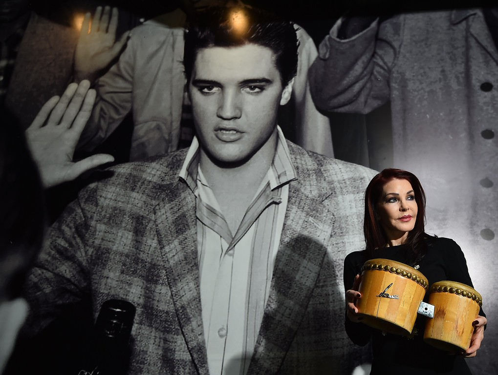 . US actress Priscilla Presley poses with a pair of bongos which she gifted to Elvis Presley during a photocall for the \'Elvis at the O2\' exhibition in in London on December 15, 2014.         (BEN STANSALL/AFP/Getty Images)
