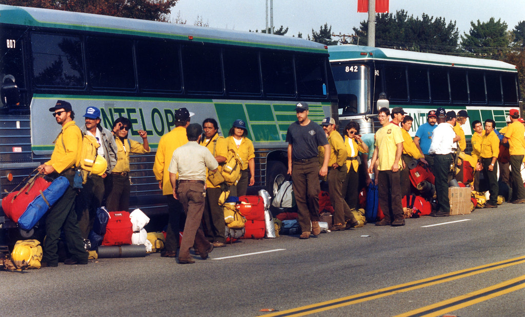 . Firefighters wait to board buses in Malibu that will take them to a new base.   (10/31/93)   Los Angeles Daily News file photo