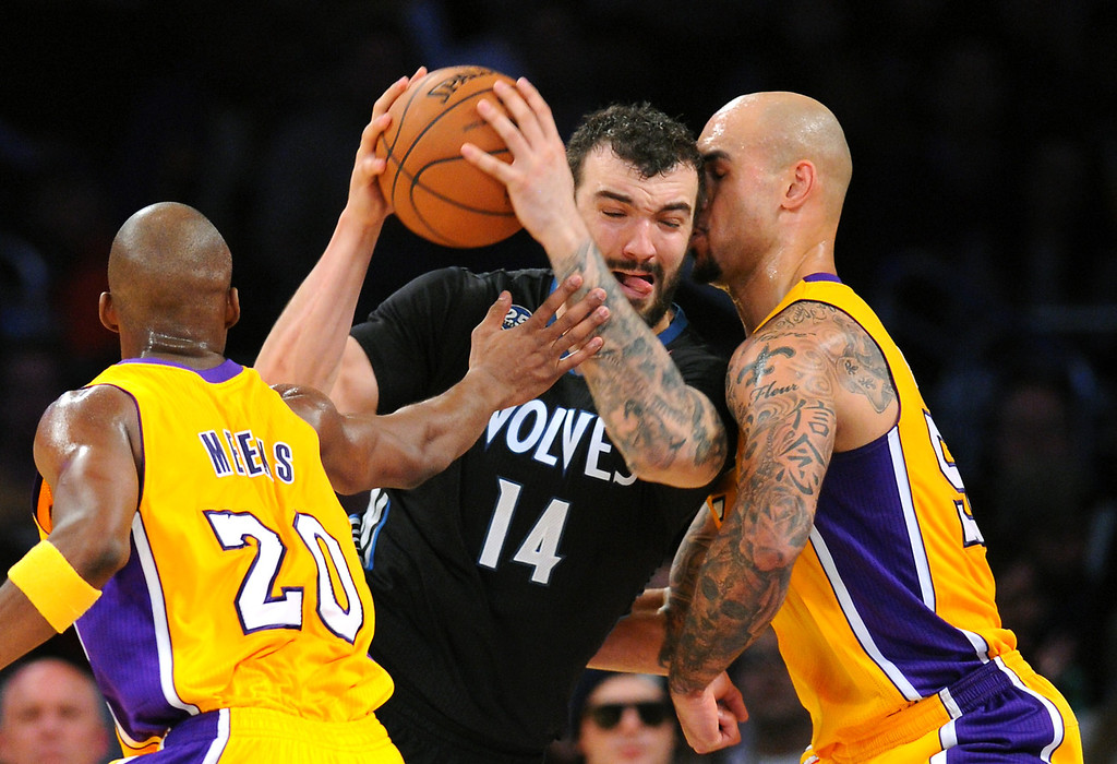 . Timberwolves center Nikola Pekovic plows through the Lakers\' Jodie Meeks, left, and Robert Sacre in the first half, Friday, December 20, 2013, at Staples Center. (Photo by Michael Owen Baker/L.A. Daily News)