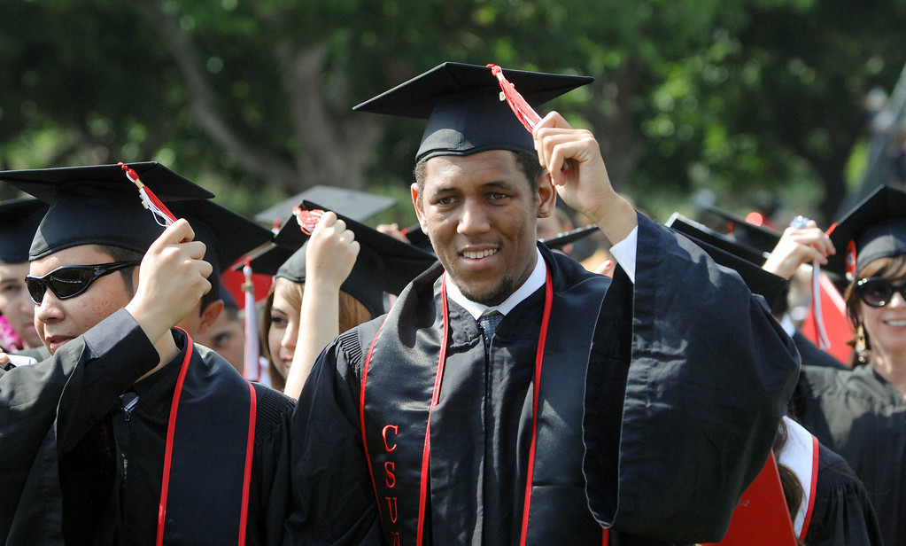 . Chris Lee, center, moves his tassel to the left side at the end of the CSUN the commencement ceremony, Tuesday, May 21, 2013. (Michael Owen Baker/L.A. Daily News)