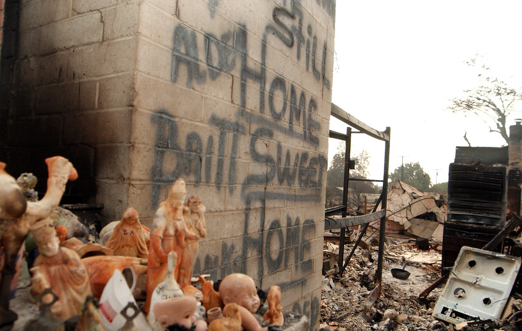 """. Ten years ago this month the arson caused Old Fire, fanned by Santa Ana winds burned thousands of acres, destroyed hundreds of homes and caused six deaths. The fire burned homes in San Bernardino, Highland, Cedar Glen, Crestline, Running Springs and Lake Arrowhead and forced the evacuation of thousand of residents. A sign spray painted on the wall of a San Bernardino home destroyed by fire reads \""""Still Home Sweet Home.\"""" (Staff file photo/The Sun)"""
