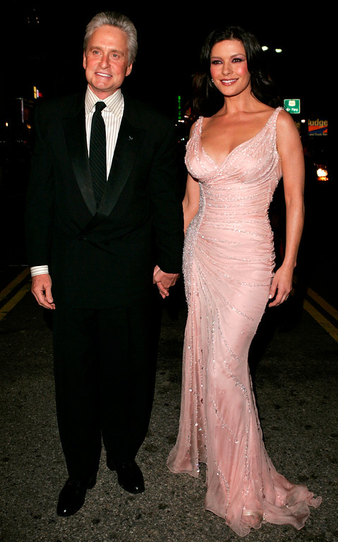". Cast member Catherine Zeta-Jones, right, arrives with husband Michael Douglas for the premiere of ""Ocean\'s Twelve,\"" at the Grauman\'s Chinese Theatre in the Hollywood section of Los Angeles, Wednesday, Dec. 8, 2004. (AP Photo/Kevork Djansezian)"