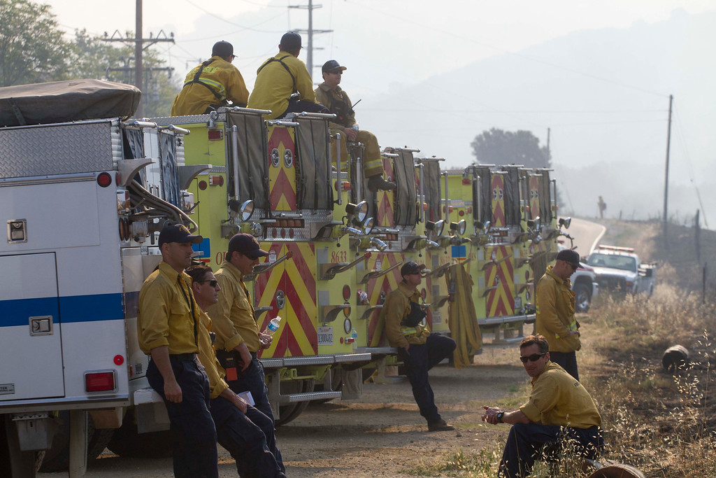 . Firefighters take a rest along a hillside in Hidden Valley, Calif., Saturday, May 4, 2013. High winds and withering hot, dry air was replaced by the normal flow of damp air off the Pacific, significantly reducing fire activity.  (AP Photo/Ringo H.W. Chiu)