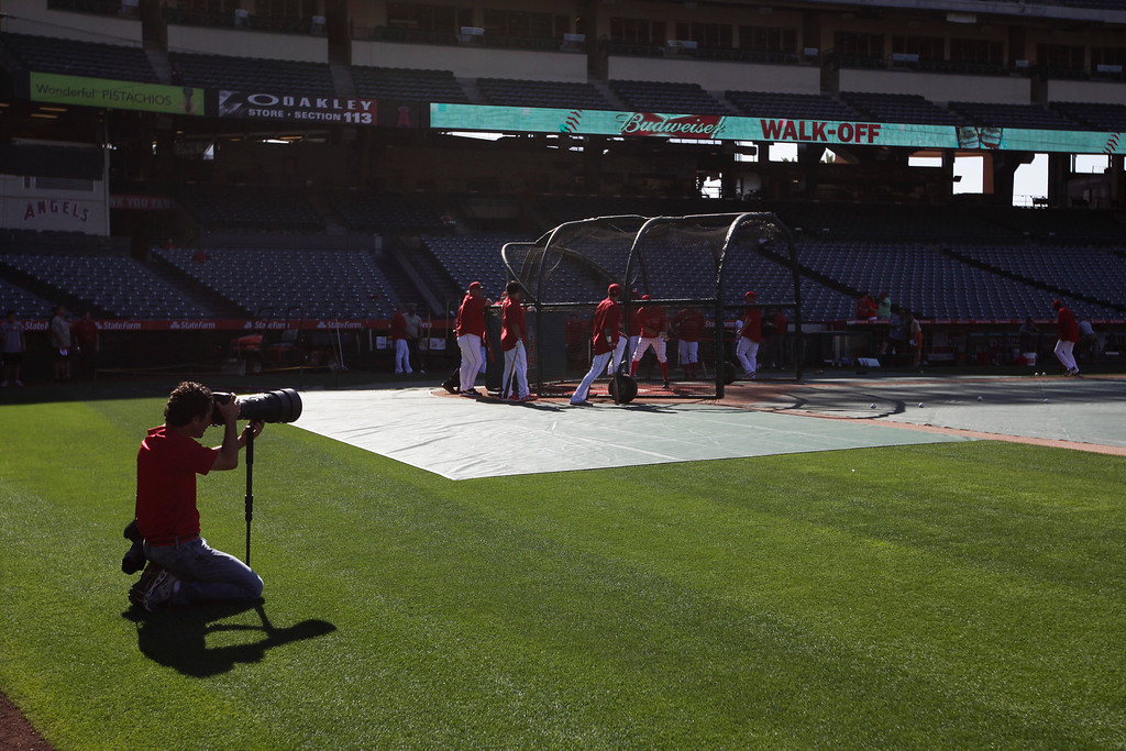 . Los Angeles Angels team photographer Matt Brown, right, takes pictures during practice for a baseball game against the Seattle Mariners in Anaheim, Calif., Tuesday, June 18, 2013. (AP Photo/Jae C. Hong)