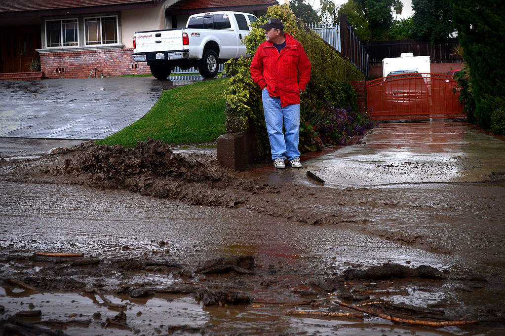. Resident Bob Roset keeps his eye on swift water rushing down Rainbow Drive in Glendora as the rainstorm starts up again Saturday afternoon, March 1, 2014. The neighborhood sits below the Colby Fire burn area. Resident Tom Tice said this was the most water and mud he\'s seen in three days of the storm. (Photo by Sarah Reingewirtz/Pasadena Star-News)