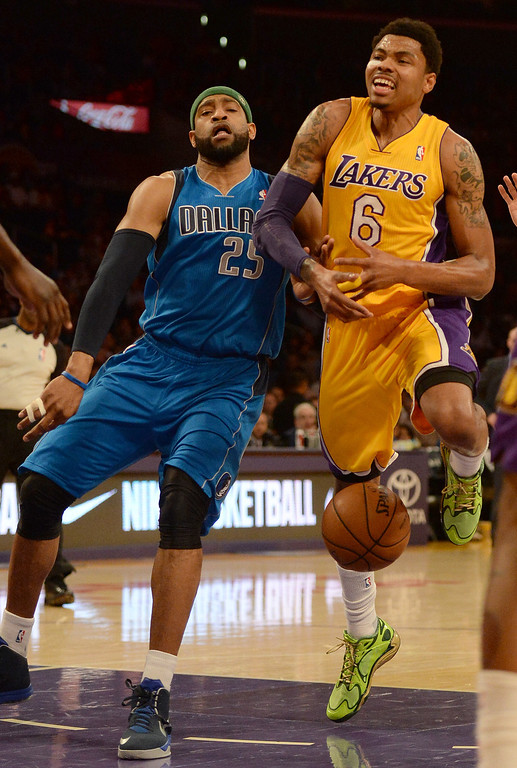. Los Angeles Lakers guard Kent Bazemore (6) is fouled by Dallas Mavericks guard Vince Carter (25) in the first quarter during an NBA basketball game in Los Angeles, Calif., on Friday, April 4, 2014.  (Keith Birmingham Pasadena Star-News)