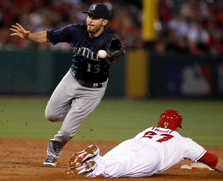 . Seattle Mariners second baseman Dustin Ackley, left, reaches for the late throw as Los Angeles Angels\' Mike Trout (27) steals second base in the third inning during a baseball game Tuesday, May 21, 2013 in Anaheim. (AP Photo/Alex Gallardo)