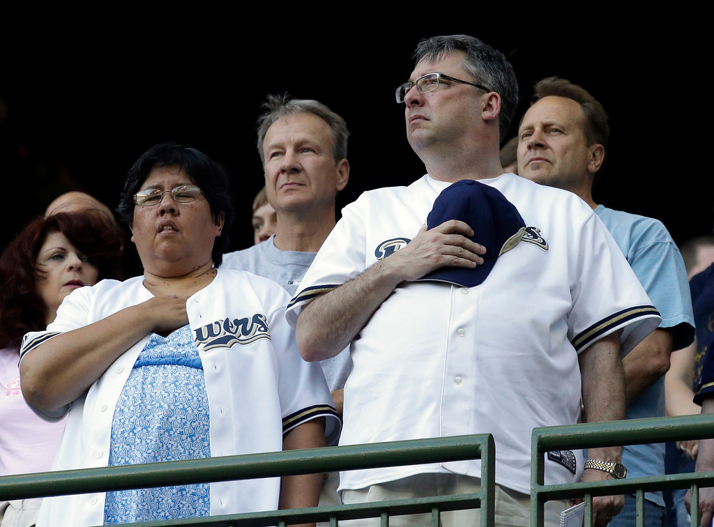. Fans pause during a moment of silence for the victims of the Oklahoma tornado before the baseball game between the Milwaukee Brewers and the Los Angeles Dodgers Tuesday, May 21, 2013, in Milwaukee. (AP Photo/Morry Gash)