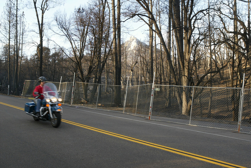 . CUYAMACA RANCHO STATE PARK, CA, NOVEMBER 5:  A motorcyclist passes a burned forest standing behind a fence intended to keep cars from pulling to the side of the road in Cuyamaca Rancho State Park, which has been closed and may not open until next spring or beyond, on November 5, 2003 in eastern San Diego County. The popular 26.000-acre mountain preserve park burned in the biggest fire in state history, the 280,000-acre Cedar Fire that killed at least 14 people and destroyed thousands of homes. The fire was contained, or surrounded by firelines, yesterday.     (Photo by David McNew/Getty Images)