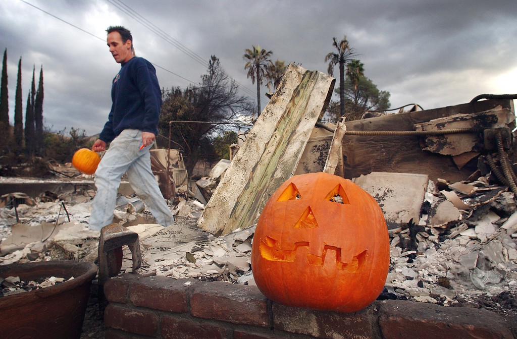 """. Ten years ago this month the arson caused Old Fire, fanned by Santa Ana winds burned thousands of acres, destroyed hundreds of homes and caused six deaths. The fire burned homes in San Bernardino, Highland, Cedar Glen, Crestline, Running Springs and Lake Arrowhead and forced the evacuation of thousand of residents. Todd Stewart brings out a pumpkin from the back yard to curb and places it in front of his mother\'s home along Del Rosa Avenue, in San Bernardino. \""""Every year since 1971 there have been two jack-o-lanterns in front of our house,\"""" Stewart said. (Staff file photo/The Sun)"""