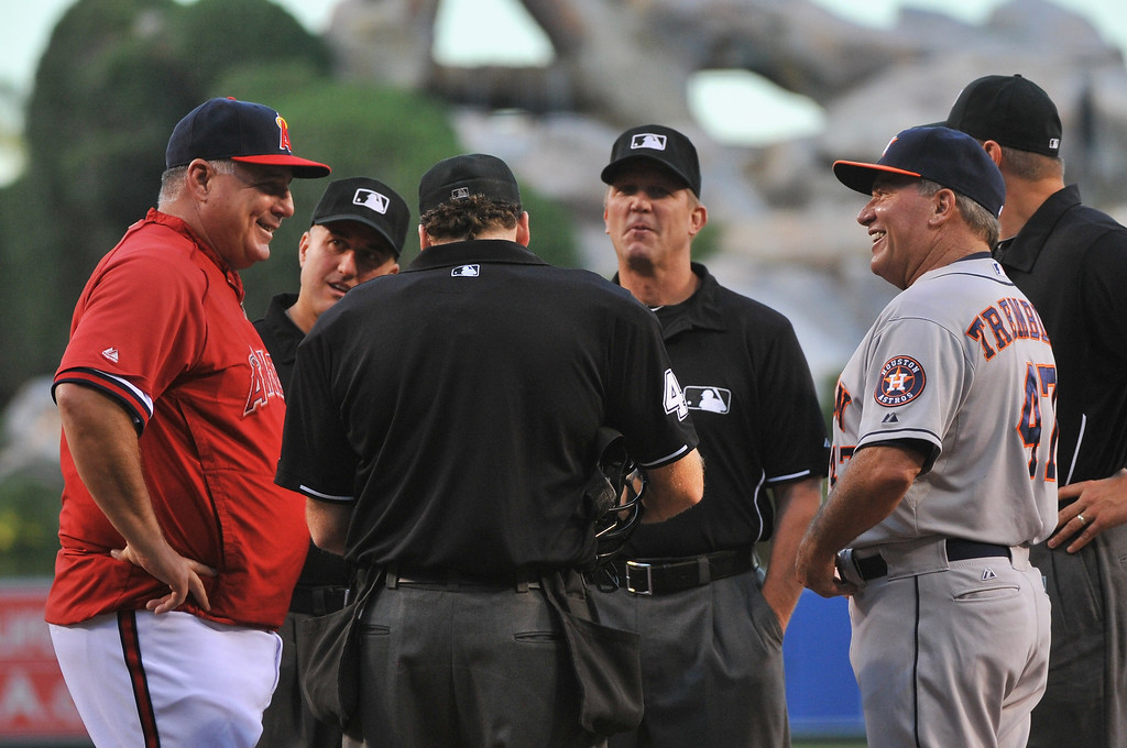 . ANAHEIM, CA - AUGUST 16:  Manager Mike Scioscia #14 of the Los Angeles Angels of Anaheim and third base coach Dave Trembley #47 of the Houston Astros talk with the umpires before a game at Angel Stadium of Anaheim on August 16, 2013 in Anaheim, California.  (Photo by Jonathan Moore/Getty Images)