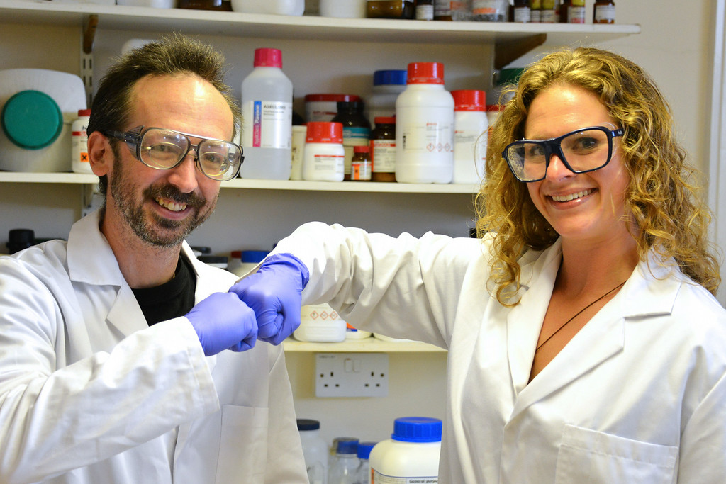 . In this undated photo provided by Prifysgol Aberystwyth University researchers David Whitworth, left, and Sara Mela, pose for photo in the lab at Prifysgol Aberystwyth University in Aberystwyth, Wales. According to results published online Monday, July 28, 2014, in the American Journal of Infection Control the researchers found that the knocking of knuckles, fist bump, spreads only one-twentieth the amount of bacteria that a handshake does. (AP Photo/Prifysgol Aberystwyth University)