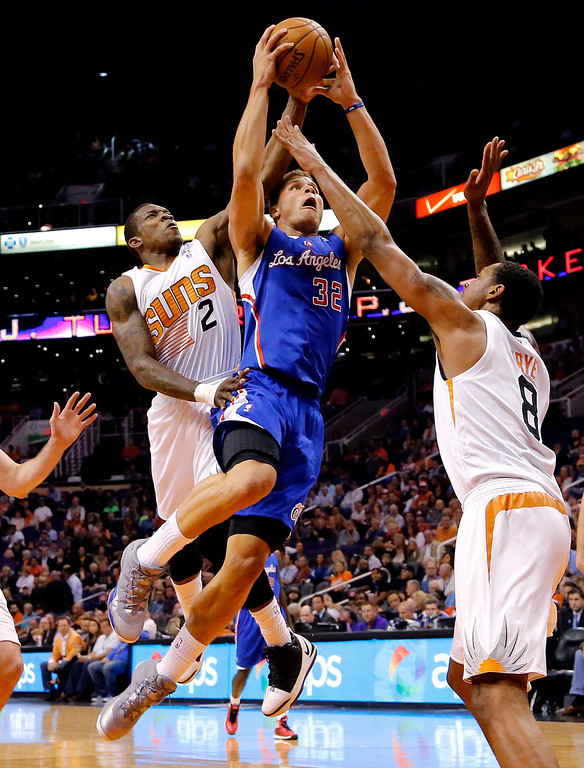 . Los Angeles Clippers forward Blake Griffin (32) drives against Phoenix Suns guard Eric Bledsoe (2) forward Channing Frye (8) during the first half of an NBA basketball game on Wednesday, April 2, 2014, in Phoenix. (AP Photo/Matt York)