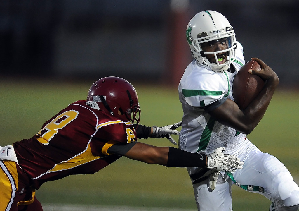 . Monrovia quarterback Deshawn Potts (1) runs for a first down past Arcadia\'s Nico Canto (8) in the first half of a prep football game at Arcadia High School in Arcadia, Calif. on Friday, Sept. 13, 2013.   (Photo by Keith Birmingham/Pasadena Star-News)