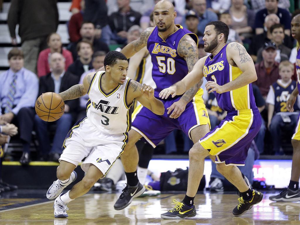 . Utah Jazz\'s Trey Burke (3) drives on Los Angeles Lakers\' Robert Sacre (50) and Jordan Farmar (1) in the second half during an NBA basketball game Monday, April 14, 2014, in Salt Lake City, Utah. (AP Photo/Rick Bowmer)