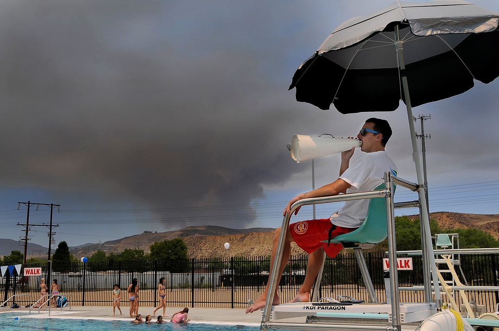 . Lifeguard Peter Szymanski keeps an eye on swimmers. The Powerhouse fire that is burning north of Santa Clarita, is visible from the Castaic Sports Complex Aquatic Center. Castaic, CA 5/31/2013(John McCoy/LA Daily News)