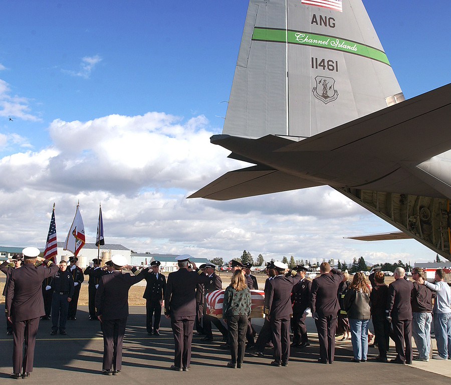 . EL CAJON, CA - NOVEMBER 3:  An honor guard salutes as the casket of firefighter Steven Rucker is carried into the cargo area of a California Air National Guard C-130 at Gillespie Field Airport November 3, 2003 in El Cajon, California. Rucker dies October 29, 2003 battling the Cedar Fire, one of California\'s largest wild fires.  (Photo by Alex J. Koenig/U.S. Air Force via Getty Images)
