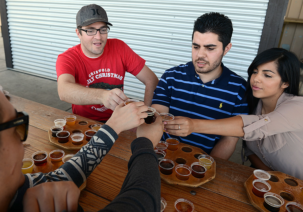 . Mike Munoz, 29, of Corona, from the left, Joel Sheffer, 28, of Redlands, Navied Jabbari, 26, of San Jose and Brittany Jimenez, 25, of Mentone toast with samples of Hanger 24 beer. Local restaurants and businesses, like Hanger 24 Brewery and Redlands Cab Company, are teaming up with the City of Redlands, Redlands police department and the San Bernardino County District Attorney\'s office to help curb drunk driving in Redlands. From December 21, 2013 through January 1, 2014 Responsible Redlands will provide free rides home from local Redlands bar businesses, up to four miles. (Photo by Rick Sforza/Redlands Daily Facts)