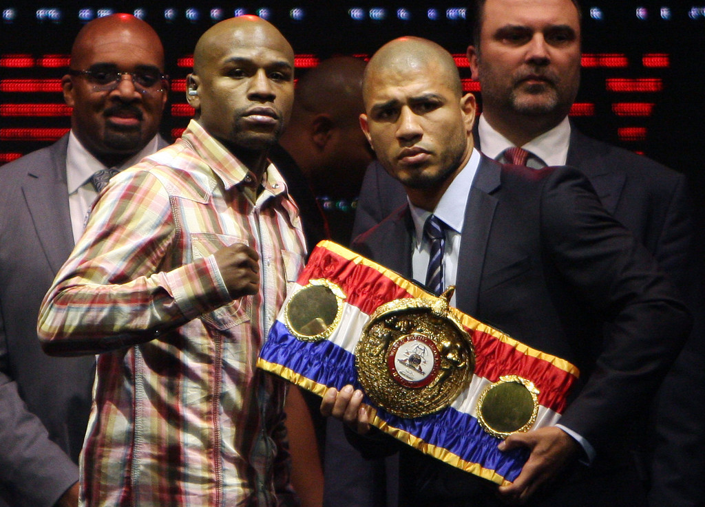 . Miguel Cotto, the reigning WBA super welterweight champion, right, and boxer Floyd Mayweather Jr., of the U.S., pose for a photo during a news conference in San Juan, Puerto Rico, Monday Feb. 27, 2012. Mayweather and Cotto will face-off in a Cinco de Mayo matchup in Las Vegas. Mayweather, the undefeated seven-time world champion in five weight classes, will turn 35 this month. He will step up in weight to fight Cotto, 31, a three-division champion from Puerto Rico. (AP Photo/Ricardo Arduengo)