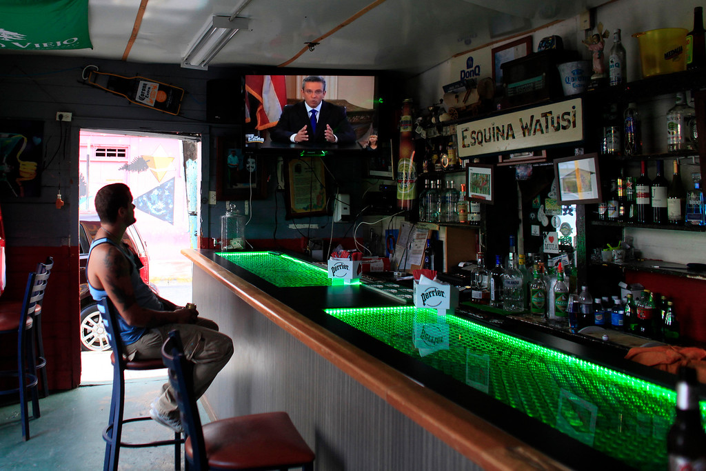 . A man in a local bar watches Puerto Rico�s governor Alejandro Garcia Padilla on television delivering an address on the state of the island\'s finances, in San Juan, Puerto Rico, Monday, June 29, 2015. The governor said that he will form a financial team to negotiate with bondholders on delaying debt payments and then restructuring $72 billion in public debt that he says the island can\'t repay. (AP Photo/Ricardo Arduengo)