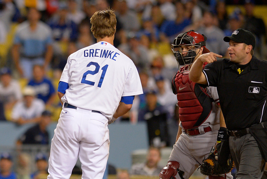 . Arizona Diamondbacks starting pitcher Ian Kennedy, not seen, is thrown out of the game by home plate umpire Clint Fagan, right, as catcher Miguel Montero, center, looks on after hitting Los Angeles Dodgers\' Zack Greinke, left, with a pitch during the seventh inning of their baseball game, Tuesday, June 11, 2013, in Los Angeles.  (AP Photo/Mark J. Terrill)