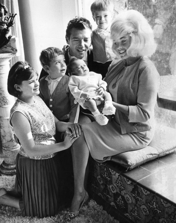 ". Photograph caption dated February 28, 1964 reads, ""Mama Jayne with Mariska, above, and same pair surrounded by, from left, Jayne Marie, Mickey Jr., Mickey Sr. and Zoltan. --As George Brich took this Valley Times photo, Hargitay asked Jayne, \'Don\'t you feel like Mother Goose?\'\"". One of two images featured on the front page of the Valley Times article, \""The Two Lives of Jayne\"". Mariska Hargitay is now an actress, well known for her role as crime detective Olivia Benson on the NBC television drama series, \""Law & Order: Special Victims Unit\"".   (Los Angeles Public Library)"