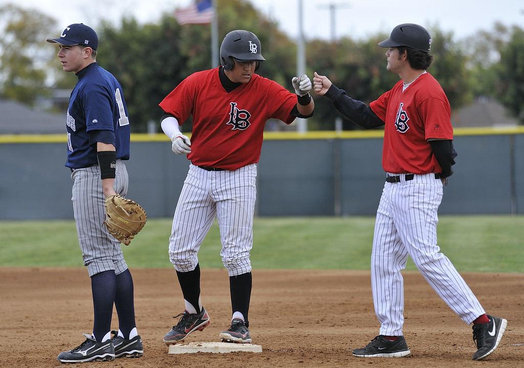 . Long Beach City College\'s Jaime Valle (18), center, gets a fist bumps after singling against Cerritos College during their game in Long Beach, Calif. on March 6, 2012..
