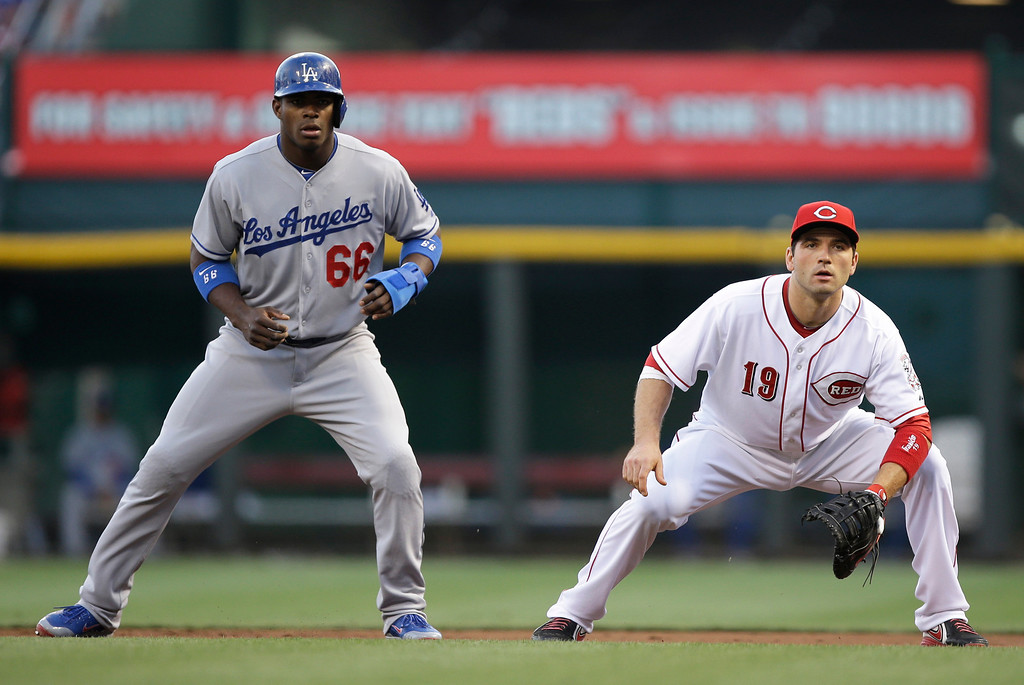 . Los Angeles Dodgers right fielder Yasiel Puig (66) leads off first base as Cincinnati Reds first baseman Joey Votto (19) waits for the pitch in the first inning of a baseball game, Friday, Sept. 6, 2013, in Cincinnati. (AP Photo/Al Behrman)