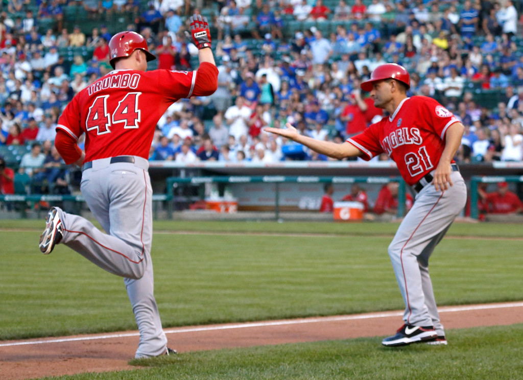 . Los Angeles Angels third base coach Dino Ebel greets Mark Trumbo at third after Trumbo\'s home run off Chicago Cubs starting pitcher Jeff Samardzija during the first inning of an interleague  baseball game Wednesday, July 10, 2013, in Chicago. (AP Photo/Charles Rex Arbogast)
