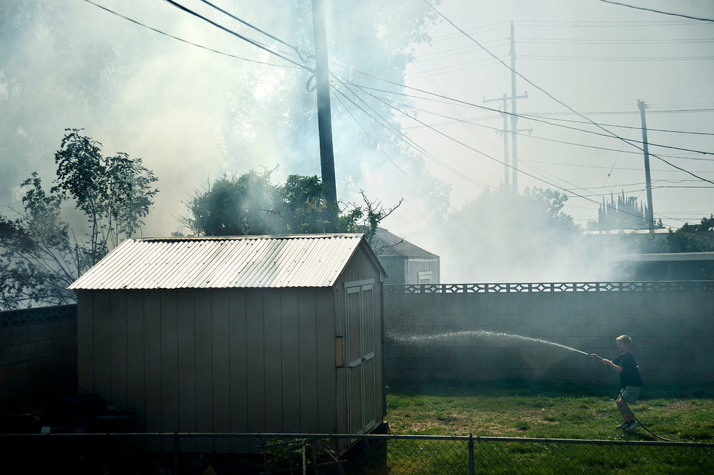 . A boy sprays water along the fence of his backyard during a brushfire in the 6000 block of Portsmouth Street in Chino on Wednesday, May 1, 2013. The wind driven fire burned several fences and power poles along the soundwall north of the 60 Freeway between Magnolia Ave and Oak Ave.  (SGVN/Staff photo by Watchara Phomicinda)