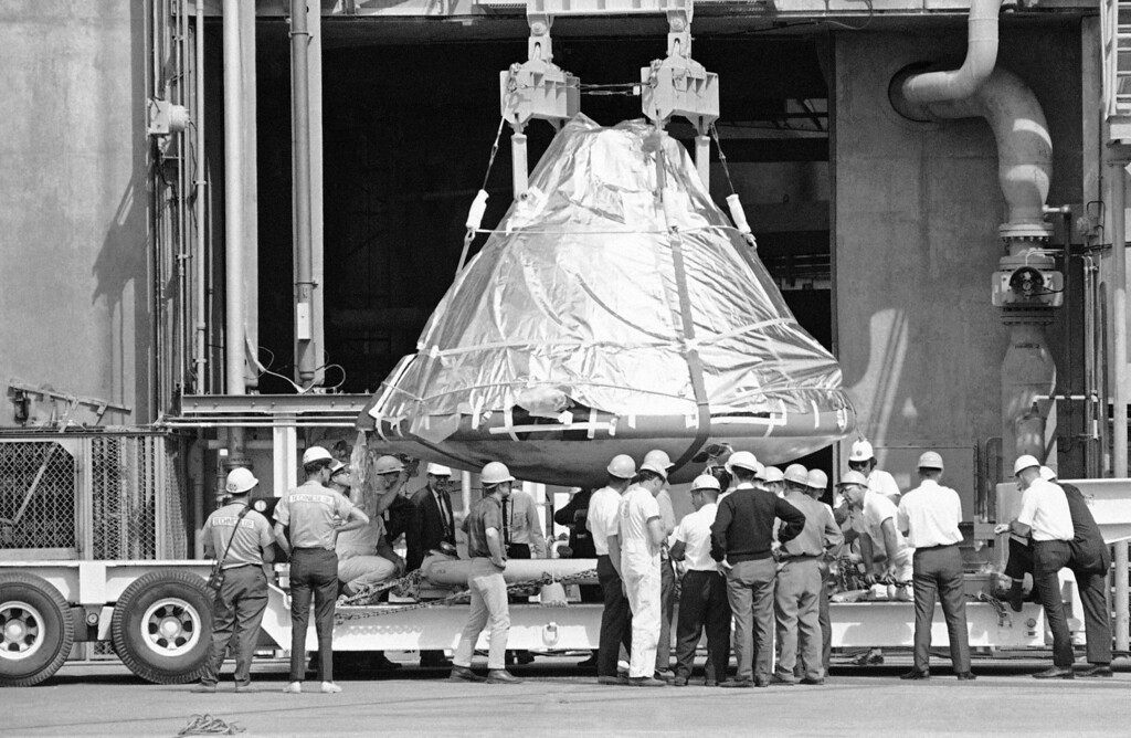 . Technicians and officials inspect the aluminum covered Apollo 1 spacecraft after it was lowered from its booster at pad 34 at Cape Kennedy, Florida on Feb. 17, 1967. Astronauts Virgil Grissom, Edward White and Roger Chaffee, lost their lives when a flash fire raced through the spacecraft on January 27. For the next several days the vehicle will be examined in detail by investigators probing to find out what caused the tragedy. (AP Photo/Jim Kerlin/Pool)