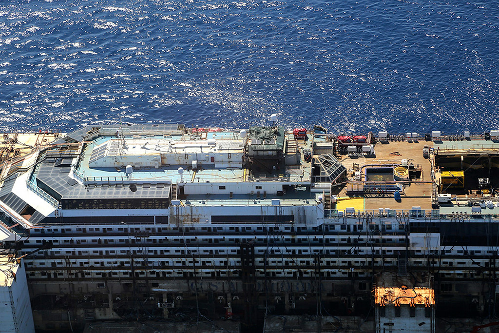 . In this aerial picture provided by the Italian Civil Protection Department, the wreck of the Costa Concordia is towed away from the tiny Tuscan island of Isola del Giglio,  Italy, Wednesday, July 23, 2014. The Costa Concordia cruise liner has begun its final voyage away from the tiny Italian island where it capsized on Jan. 13, 2012, killing 32 people. (AP Photo/Courtesy of the Italian Civil Protection Department, ho)