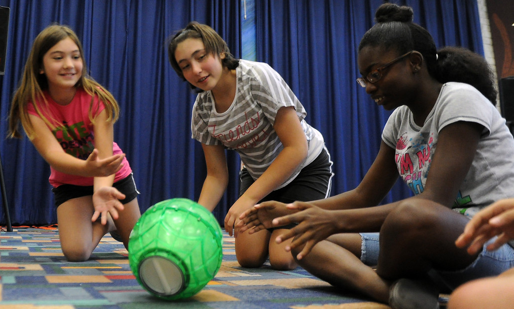 . Ten year-old Kayla Scoria, left, rolls the ice cream ball as thirteen year-old Kaitlyn Scoria, center, and thirteen year-old Myra George, right, look on during a Summer Teen Reading Club ice-cream making and tasting session at the Glendora Public Library Bidwell Forum on Wednesday, July 17, 2013 in Glendora, Calif.   (Keith Birmingham/Pasadena Star-News)