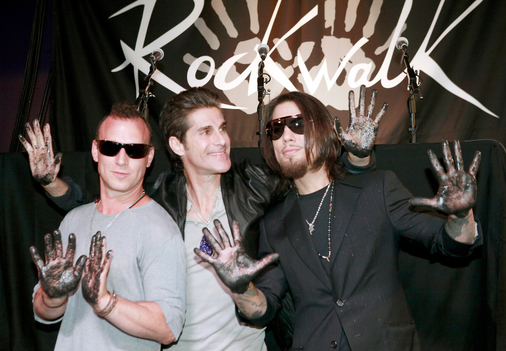 . Jane\'s Addiction band members, from left, Stephen Perkins, Perry Farrell and Dave Navarro, react after placing their hands in cement following an induction ceremony into the Rock Walk in Los Angeles, Wednesday June 1, 2011.  (AP Photo/Nick Ut)