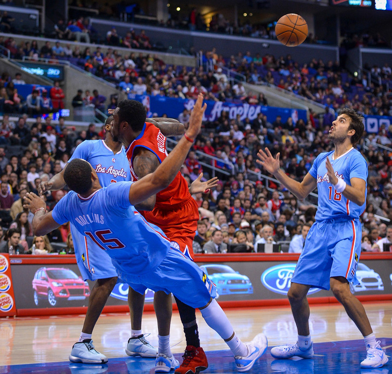 . Clippers� Ryan Hollins is fouled by 76ers� Tony Wroten as Sasha Vujacic looks on at Staples Center Sunday.  The Clippers defeated the 76ers 124-78.  ( Photo by David Crane/Los Angeles Daily News )