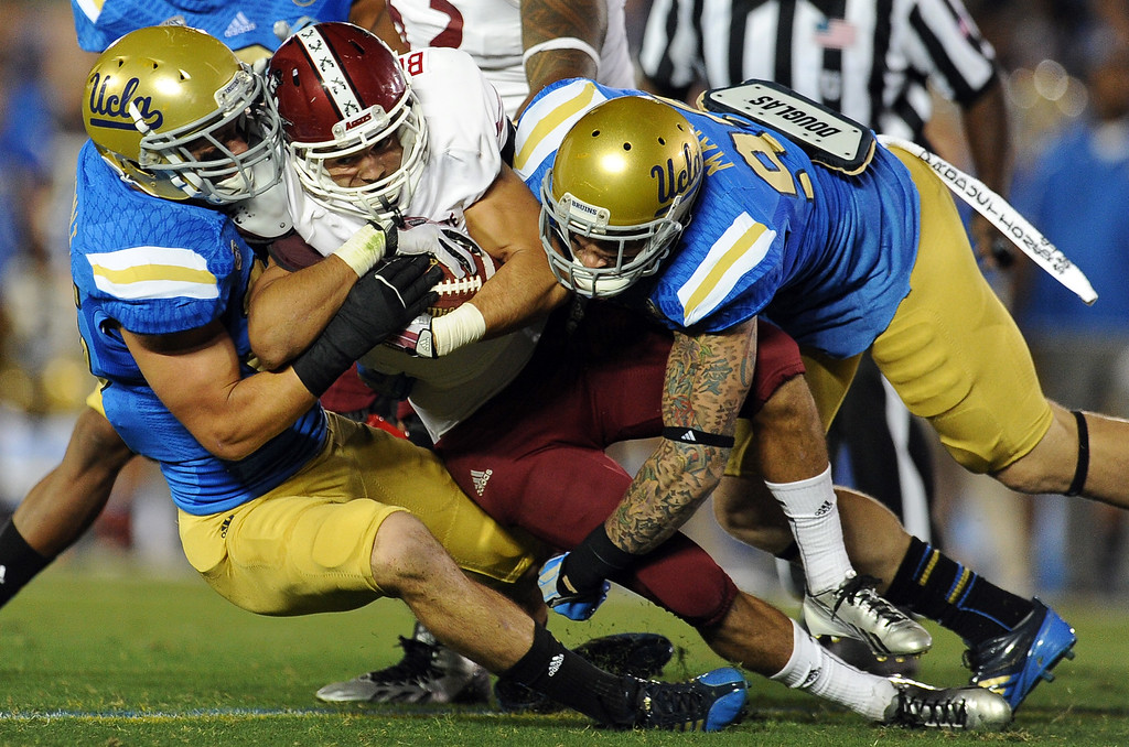 . UCLA defense tackles New Mexico State running back Brandon Betancourt (21) for a loss of yards during the first half of their college football game in the Rose Bowl in Pasadena, Calif., on Saturday, Sept. 21, 2013.   (Keith Birmingham Pasadena Star-News)