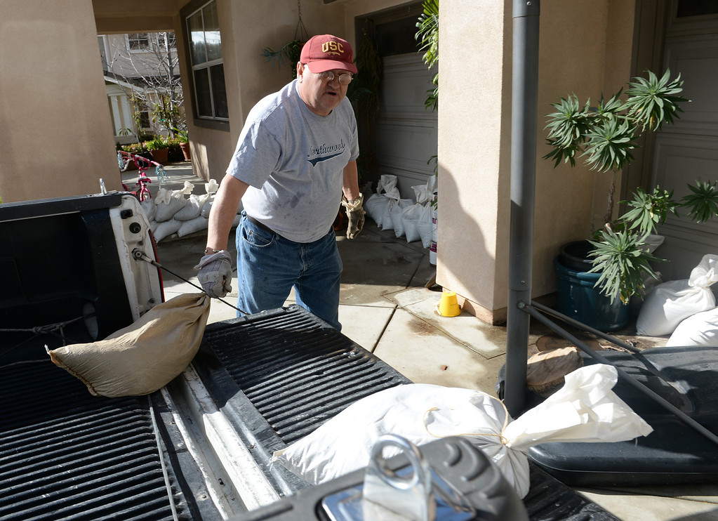 . Lorenzo Tatone places sand bags around his home on Ridge View Drive in case the mud from the hills slides down in Azusa on Thursday February 27, 2014. (Staff Photo by Keith Durflinger/San Gabriel Valley Tribune)