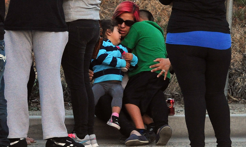 . Myra Velasquez, center, wife of Efren Velasquez hugs children in front of a make shift memorial for her husband and two children who were killed in a late Thursday night crash along the 3500 block of San Gabriel River Road on Friday, June 14, 2013 in Industry, Calif. Three others were injured in the crash.  (Keith Birmingham/Pasadena Star-News)