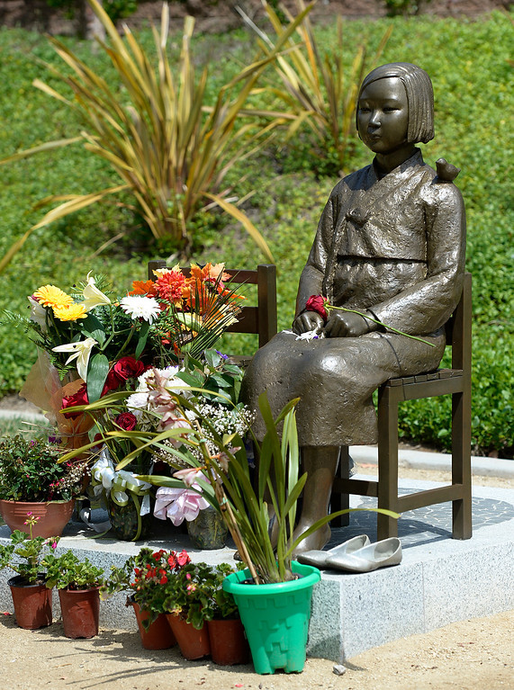 . Adorned by flowers and other offerings, the Comfort Women statue sits in Glendale Central Park. Los Angeles residents and GAHT-U.S., a nonprofit corporation, filed a lawsuit stating asking that the statue, which honors women forced to work as sex slaves during World War II, be removed because it symbolizes disapproval of Japanese women. Glendale, CA. 4/18/2014(Photo by John McCoy / Los Angeles Daily News)