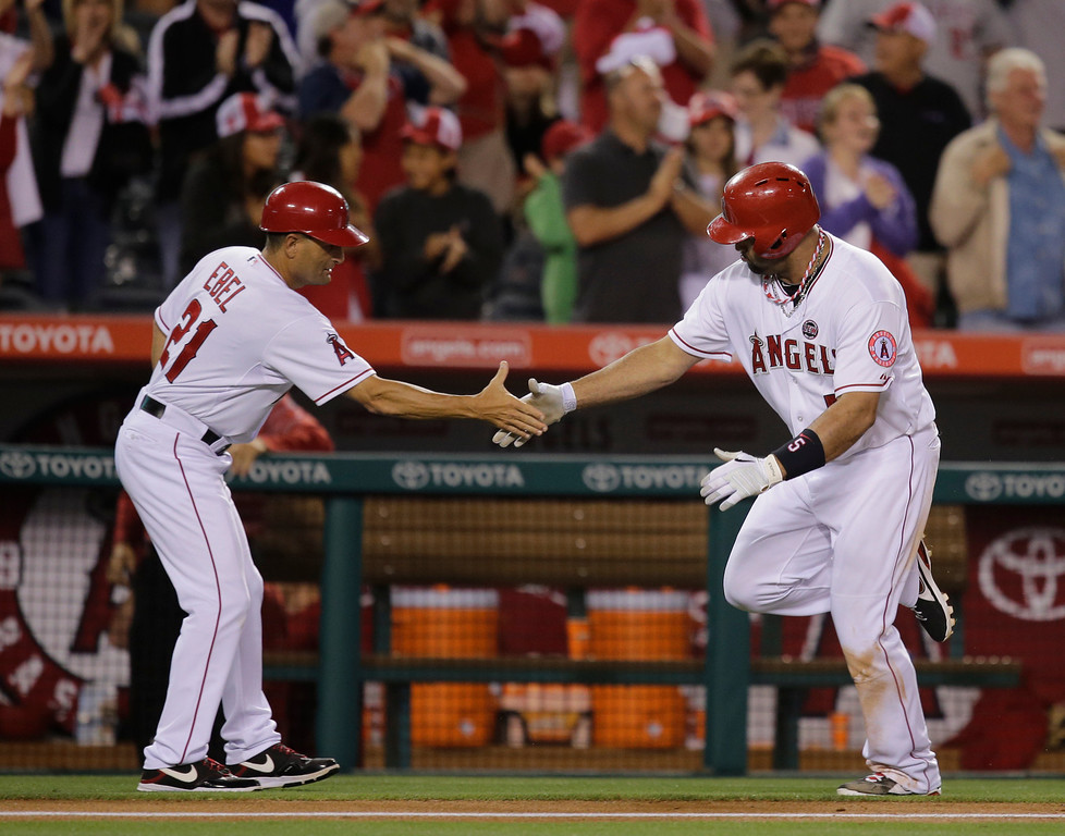 . Los Angeles Angels\' Albert Pujols, right, is greeted by Los Angeles Angels third base coach Dino Ebel after hitting a home run during the eighth inning of a baseball game against the Seattle Mariners in Anaheim, Calif., Tuesday, June 18, 2013. (AP Photo/Jae C. Hong)
