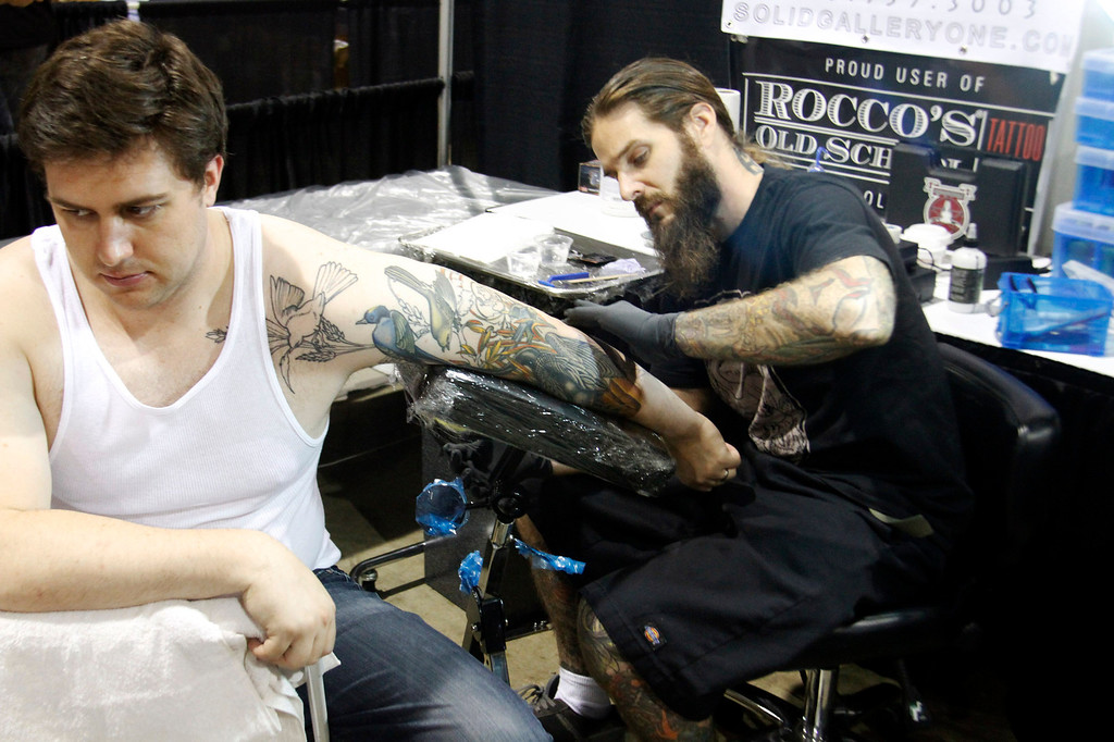 . (Correspondent Photo by James Carbone) Andrew Thompson, 32, of Los Angeles, gets a tattoo from artist Jarrett DeMartino, from Solid Gallery One in Los Angeles, during the Tattoo and Body Art Expo, the world\'s largest tattoo expo, comprised of more than 300 tattoo artists and piercers, at the Pomona Fairplex, in Pomona, Saturday, July 11, 2013.