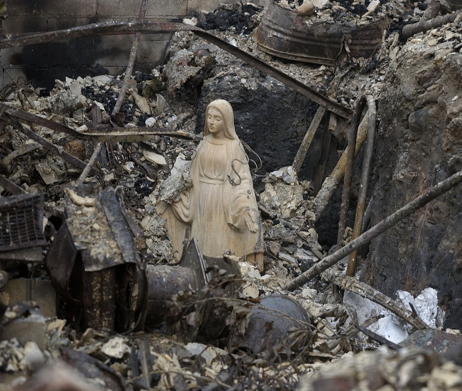 . A statue of the Virgin Mary stands among the rubble of a burned-out home in Cuyamaca, Calif. Nov. 1, 2003. The home was one of 2,200 homes destroyed in the 275,000 acre Cedar fire east of San Diego. (AP Photo/Charlie Riedel)