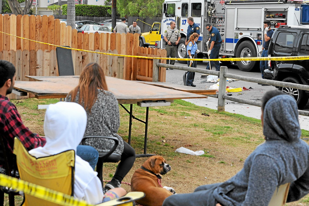 . UCSB students watch the cleanup where the gunman\'s car crashed on Del Playa Drive in Isla Vista, Saturday, May 24, 2014. (Photo by Michael Owen Baker/Los Angeles Daily News)