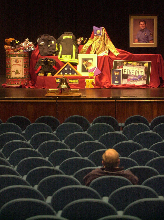. Novato Fire Chief Jeffrey Meston, bottom, sits alone inside the Marin Veterans Memorial Auditorium in San Rafael, Calif., Wednesday, Nov. 12, 2003, before the memorial service for Steven Rucker, a Novato, Calif. firefighter killed while fighting the Cedar Fire in San Diego County on Oct. 29. Meston is the chief of the department that Rucker served in. Some of Rucker\'s equipment and assorted personal mementos were placed on the stage for the service. (AP Photo/Pool, Robert Tong)