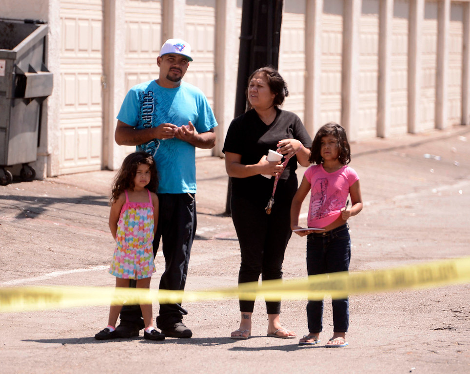 . Residents watch police investigate a double-shooting at the Orchid Lane Apartments located on the 300 block of Orchid Lane in Pomona August 11, 2013.   GABRIEL LUIS ACOSTA/STAFF PHOTOGRAPHER.