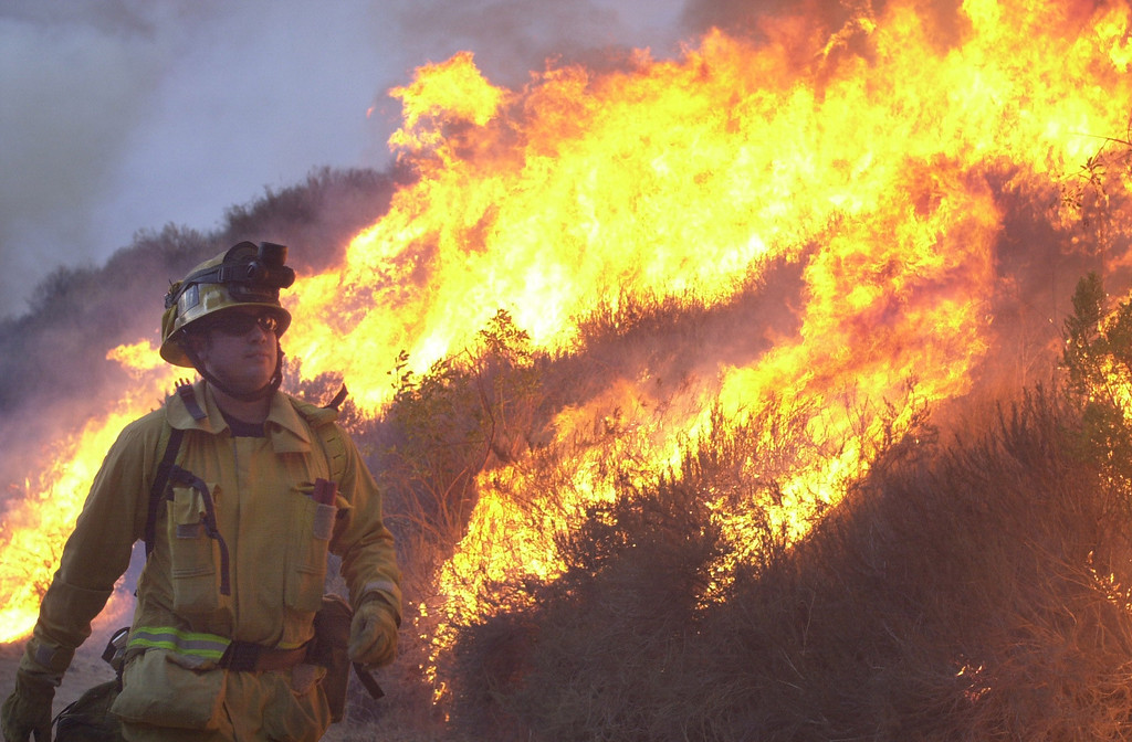 . VAL VERDE FIRE--A firefighter sets a backfire to protect homes along San Martinez Grande road Friday afternoon.    10.24.03   Photo by David Crane/Daily News