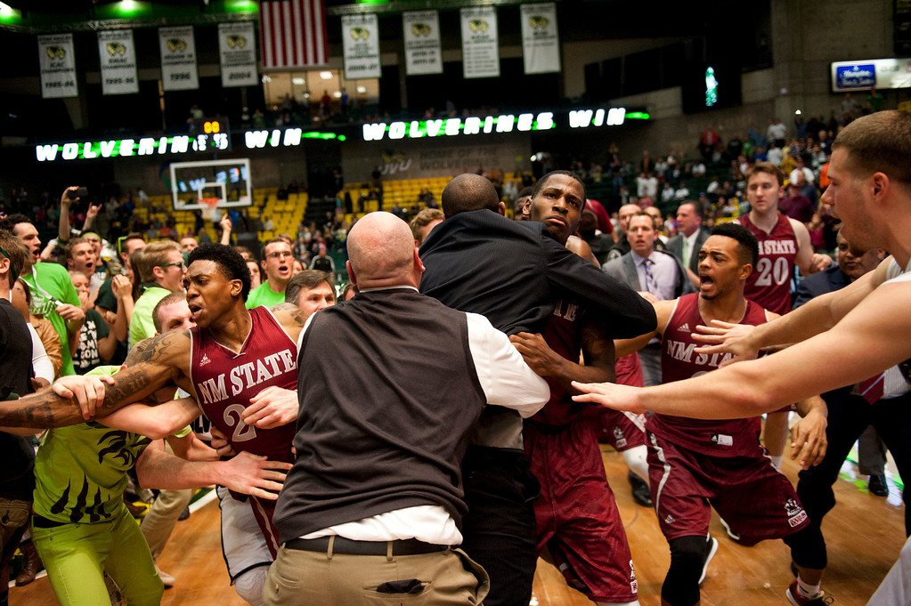 . In this Thursday, Feb. 27, 2014 photo, security, at center back to camera, try to hold back players as a wild brawl involving players and fans who came onto the court broke out when New Mexico State guard K.C. Ross-Miller hurled the ball at Utah Valley\'s Holton Hunsaker seconds after the Wolverines\' 66-61 overtime victory against the Aggies on Thursday night, Feb. 27, 2014.  (AP Photo/The Daily Herald, Grant Hindsley)
