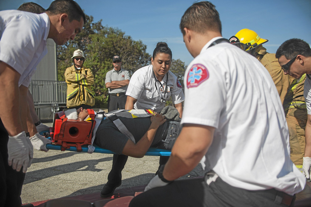 . Vanessa Sanchez, an EMT student, helps lift a mock patient onto a gurney during a crisis drill at Rio Hondo College in Whittier on Friday, May 9, 2014. (Correspondent Photo by William Camargo)