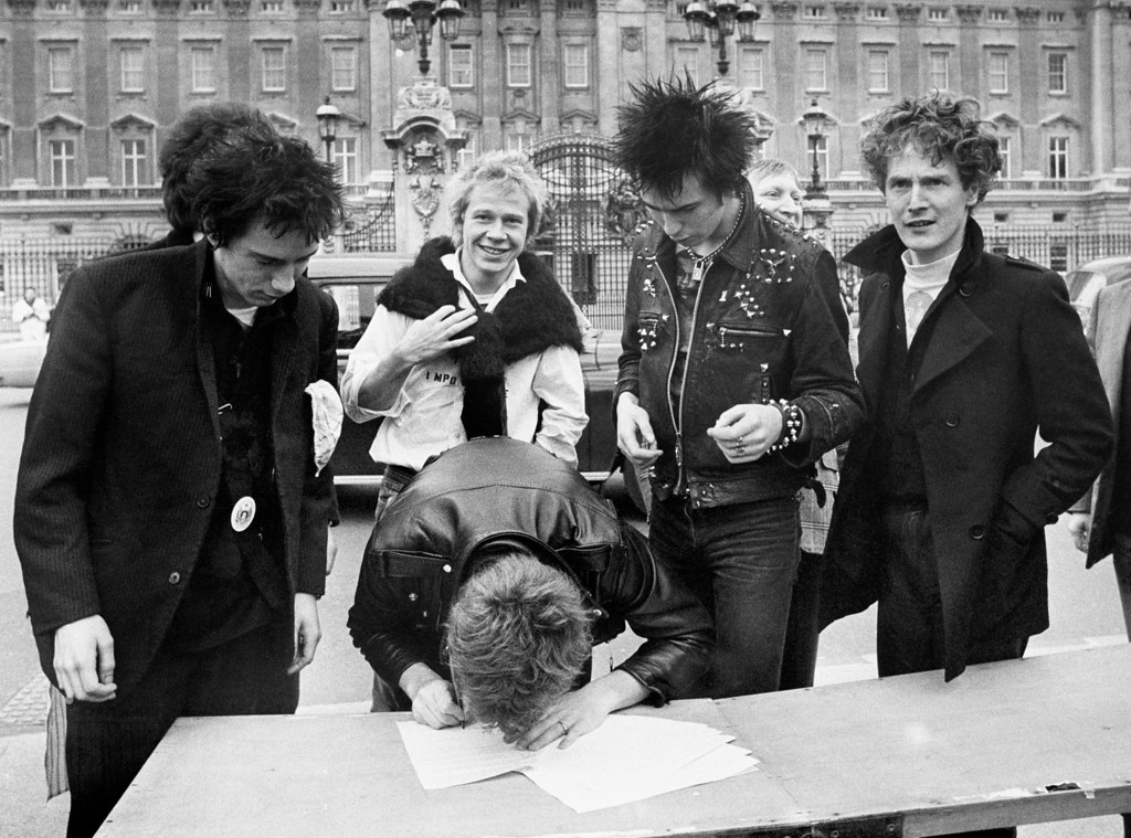 . In this March 1977 file photo, the Sex Pistols, from left: Johnny Rotten, Steve Jones (signing document), Paul Cook,  Sid Vicious and their manager Malcolm McLaren sign a new recording contract outside Buckingham Palace in London.  (AP Photo/Press Association)