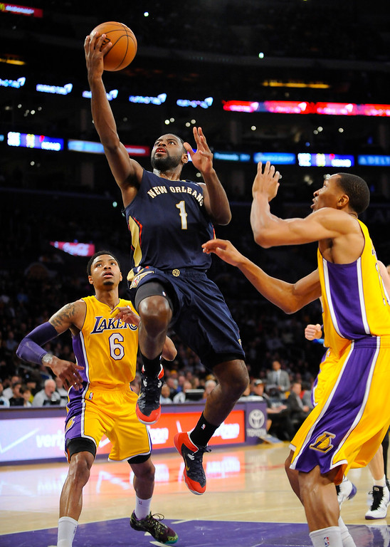 . New Orleans Pelicans forward Tyreke Evans (1) gets by Los Angeles Lakers forward Wesley Johnson, right, and guard Kent Bazemore (6) as he drives to the basket during the first half of an NBA basketball game, Tuesday, March 4, 2014, in Los Angeles.(AP Photo/Gus Ruelas)